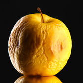 Yellow apple as problem skin concept, on black background — Stock Photo