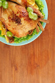 Whole roasted chicken with lettuce, grapes, oranges and spices on blue plat — Стоковое фото