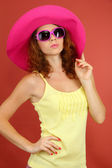 Smiling beautiful girl with beach hat and glasses on pink background — Stock Photo