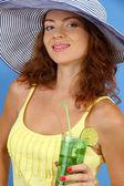 Menina bonita sorridente com chapéu de praia e coquetel em fundo azul — Foto Stock