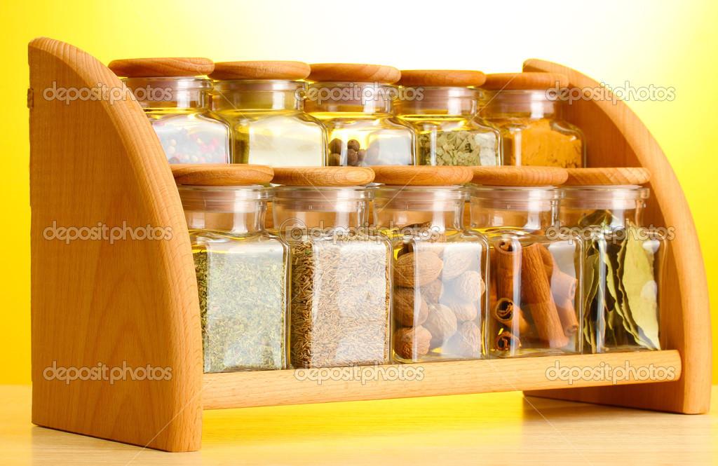 pices en poudre dans des bocaux de verre sur l 39 tag re en bois sur fond jaune photographie. Black Bedroom Furniture Sets. Home Design Ideas