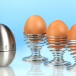 Egg timer and egg in metal stand on blue background — Stok fotoğraf