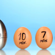 Egg timer and eggs on blue background — Stock Photo