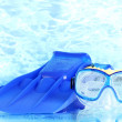 Blue flippers and mask on blue sea background - Photo