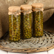 Glass jars with tinned capers in sack on white wooden background — Stock Photo #13729055