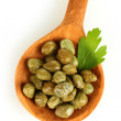 Green capers in wooden spoon on white background close-up — Stock Photo