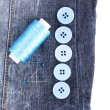Stock Photo: Colorful sewing buttons with thread on jeans