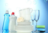 Empty clean plates, glasses and cups with dishwashing liquid and sponges on — Stock Photo