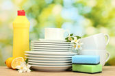 Empty clean plates and cups with dishwashing liquid, sponges and lemon on w — Stock Photo