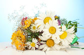 Beautiful bouquet of bright wildflowers, on wooden table on blue backgroun — Stock Photo