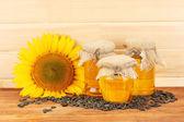 Olej słonecznikowy i słonecznik na tle drewna — Zdjęcie stockowe