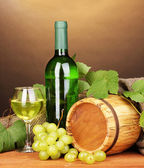 Bottle of great wine with glass and octave on wooden table on brown backgro — Stock Photo