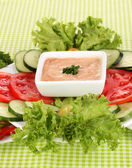 Chopped vegetables and sauce on plate on green tablecloth — Foto de Stock