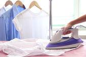 Mano de mujer planchando una camisa, sobre fondo de tela — Foto de Stock