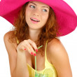 Stock Photo: Smiling beautiful girl sitting at the table with beach hat and cocktail iso