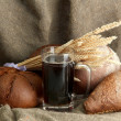 Tankard of kvass and rye breads with ears, on burlap background — Stock Photo #13730312