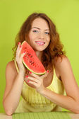 Smiling beautiful girl with watermelon on green background — Stock Photo