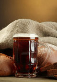 Tankard of kvass and rye breads, on wooden table on brown background — Stock Photo