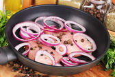 A pieces of pork with onions fried in pan with herbs, spices and cooking oi — Stock Photo