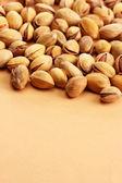 вкусные фисташковые орехи, на бежевом фоне — Стоковое фото