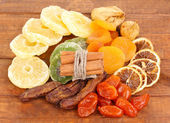 Dried fruits with cinnamon on wooden background — Stock Photo