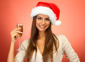 Krásná mladá žena se sklenkou šampaňského na červeném pozadí — Stock fotografie