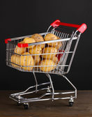 Batatas maduras no carrinho na mesa de madeira em fundo preto — Fotografia Stock