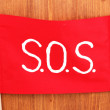 Stock Photo: SOS signal written on red cloth on wooden background