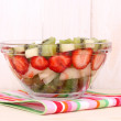 Mixed fruits and berries in glass on napkin on wooden background - Stock Photo