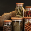 Jars with spices on wooden table on black background — Stock Photo