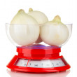 White onion n a kitchen scales isolated on white background — Stock Photo