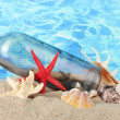 Glass bottle with note inside on sand, on blue sea background — Stock Photo #13743917
