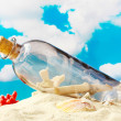 Stock Photo: Glass bottle with note inside on sand, on blue sky background