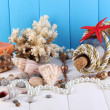 Decor of seashells on wooden table on blue wooden background — Stock Photo #13744149