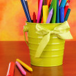 Colorful pencils and felt-tip pens in green pail on color background — Stockfoto