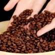 Coffee beans in hands on dark background — Stock Photo #13744497