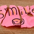 Torn paper with words Smile close-up on wooden table — Stock Photo