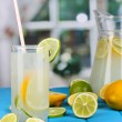 Citrus lemonade in pitcher and glass of citrus around on blue wooden table — ストック写真