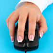 Woman's hands pushing keys of pc mouse, on blue background close-up — Stock Photo