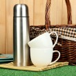 Metal thermos with cups, plates and basket on grass on wooden background — Stock Photo #13745380