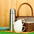 Metal thermos with cups, plates and basket on grass on wooden background — Stock Photo #13745394