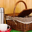 Stock Photo: Metal thermos with cup and basket on grass on wooden background