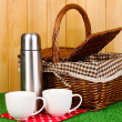 Stock Photo: Metal thermos with cups and basket on grass on wooden background