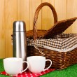 Metal thermos with cups and basket on grass on wooden background — Stock Photo #13745418