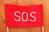 SOS signal written on red cloth on wooden background — 图库照片