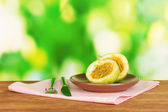 Green passion fruit in the plate on bright green background — Stock Photo