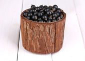 Black currant in wooden cup on wooden background — Stock Photo