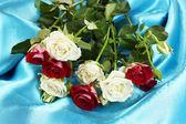 Bukett med vackra rosor på blå satin närbild — Stockfoto