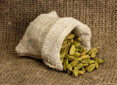 Green cardamom in sack on canvas background close-up — Stock Photo