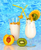 Delicious milk shakes with fruit on table on blue sea background — Stock Photo
